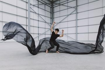 An asian male dancer in a warehouse bracing himself as silk fabric falls around him