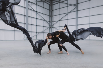 Two male dancers wrestling in a warehouse with black ink-like silk flying around them