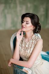 Image of elegant Brunette girl sitting in retro style armchair.