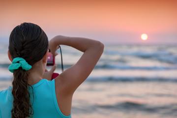 Junges Mädchen fotografiert den Sonnenuntergang mit ihrer Kamera