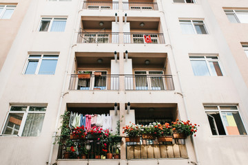 Residential building in Istanbul with balconies decorated with flowers and small Turkish flags. Turkey. Ordinary people's life. Authentic.