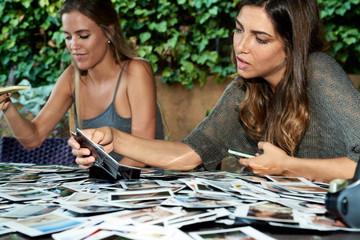 Two girlfriends choosing  photos