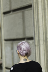 real young androgyne woman with pink hair on the street