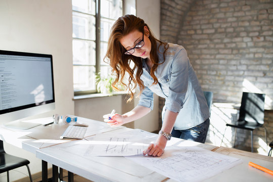 Portrait of young female architect working on project