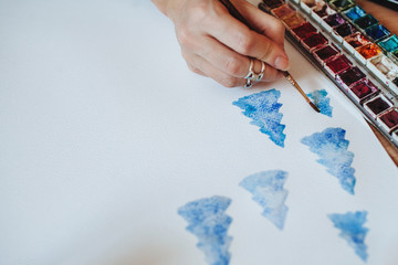 Unrecognizable female artist paints watercolor Christmas trees
