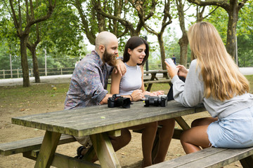 Friends with gadgets in park