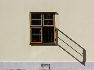 Open window throws a shadow on a wall