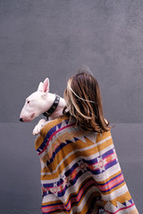 Faceless woman holding and embracing white dog.