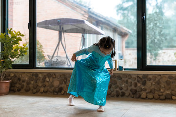 Young girl in party dress dancing at home