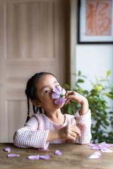 Adorable little girl holding flower at home