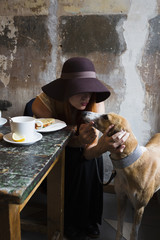 Young woman and a dog in a cafe