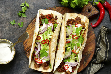 Mexican tacos with pulled beef,fresh cucumber and yogurt dressing.Top view with copy space.