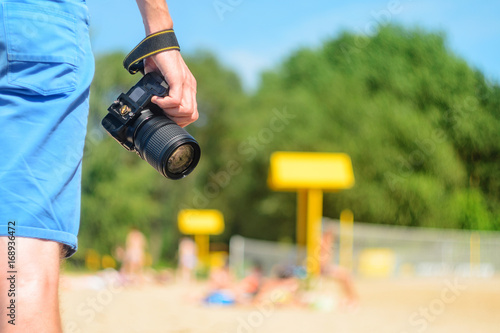 Dslr Camera In Hand In Sea Beach Background Stock Photo And Royalty