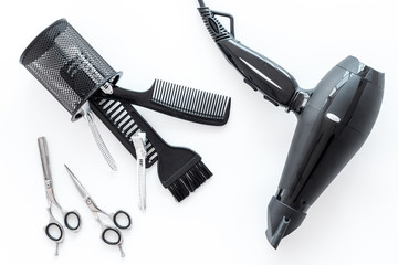 scissors with drier and hairdresser tools on white work desk