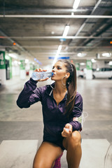 Young woman in public parking garage drinking water after fitness workout..