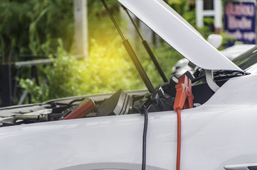 Auto mechanic uses a charging battery with electricity trough jumper cables in a car.