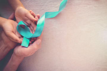 Adult and child hands holding Teal Ribbon, toning background, Ovarian Cancer, cervical Cancer, Kidney Cancer and sexual assault awareness