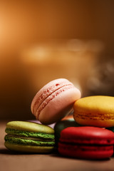 Colorful macarons cake. Closeup macaroons on color white isolated background. in coffee shop vintage color. Wooden table with flare. Retro style. Food natural background. Close up macro photo