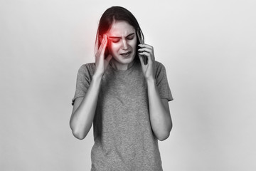 Portrait of a pretty woman  stress and headache having migraine pain. Black and white with red accent