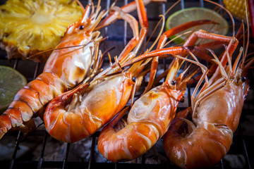 shrimp,prawn grilled on barbecue stove with lemon and pineapples