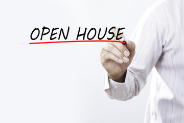 Businessman hand writing OPEN HOUSE with red marker on transparent wipe board, business concept