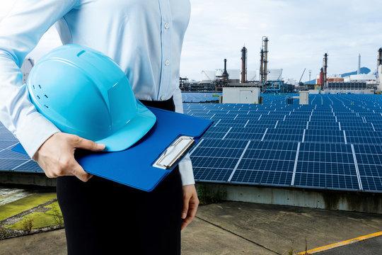 engineer holding helmet and solar power plant. renewable energy concept.