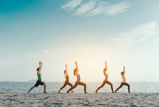 Young group man and woman yoga practice on mat relaxation in class exercise with pose fitness sport for healthy on the beach and seaside  modern city at sunrise relax