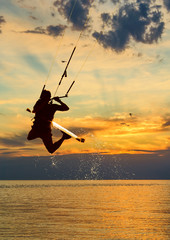 Silhouette of kitesurfer on sunset sky background