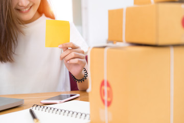 Young asian girl freelancer business private working at home office holding post it paper with laptop, note, packaging delivery online market on purchase orders to customer.