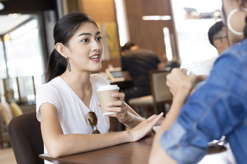 Asian Woman Drink Coffee at Cafe with Attractive Smiling Together, Woman Talking with Friend while Drink Coffee, Woman Lifestyle Concept.