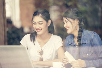 Asian Woman using Laptop at Cafe with Attractive Smiling Together, Woman Talking with Friend while using Laptop, Woman Lifestyle Concept, Vintage Tone.