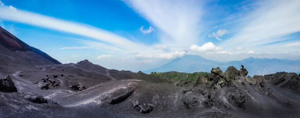 Panoramic View from the base of Volcano Pacaya with characteristic volcanic rock formations with Volcano Aqua in background