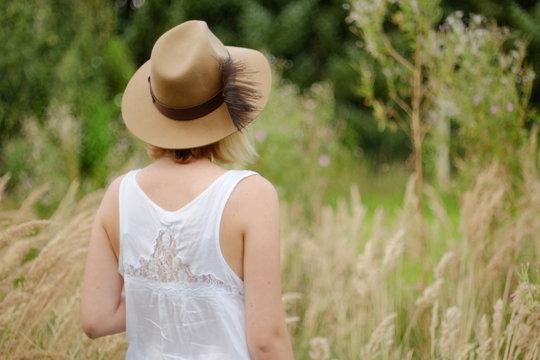 junge Frau mit Kleid und Hut in einem Feld mit Gräsern