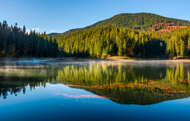 smokey lake reflect forest mountain and blue sky