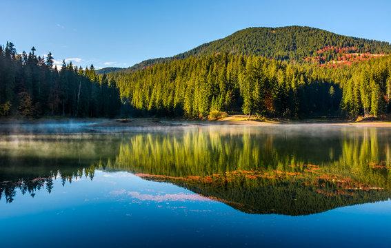 smokey lake reflect forest mountain and blue sky