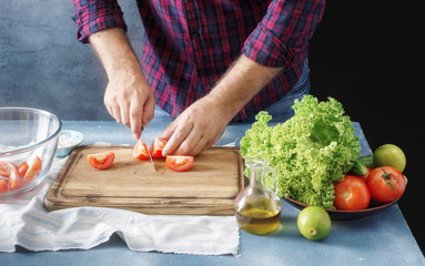Man cooking salad In the home kitchen