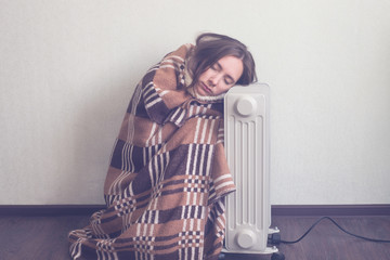 young woman in woolen plaid warm up hands over electric heater Wall mural