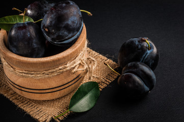 Garden plums in bowl on stone table. View with copy space