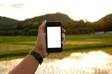 Mobile phone in the hands of a woman have a white screen for text or image input with a blurred view of field and mountain in background.