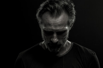 Low key dramatic portrait of mature man on black background. Beardy upset male looking down.