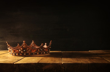 low key of beautiful queen/king crown over wooden table. vintage filtered. fantasy medieval period