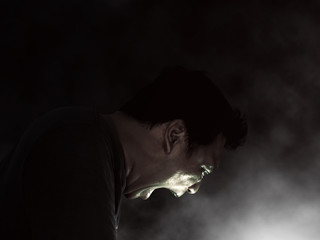 Side portrait of a shouting man, guy, Rage Scream, emotional with a dark background and smoke rising from below.