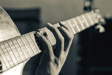 close up on hand playing guitar on black and white tone