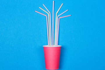 a bundle of multi-colored drinking straws in a paper Cup