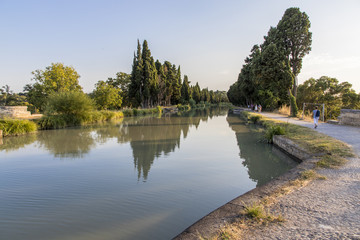 Photo sur Plexiglas Canal The Canal du Midi in Beziers at sunset, a long canal that connects the Atlantic Ocean with the Mediterranean Sea in Southern France. A world heritage site since 1996