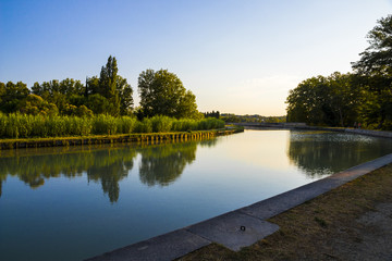 Poster Channel The Canal du Midi in Beziers at sunset, a long canal that connects the Atlantic Ocean with the Mediterranean Sea in Southern France. A world heritage site since 1996