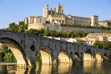 Views at sunset of the French city of Beziers, with trees and the old bridge reflected over the river Orb, and the 13th-century Cathedral of Saint Nazaire in the background