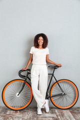 Vertical image of smiling african woman posing with bicycle
