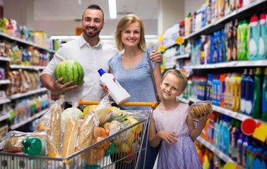 Portrait of  family standing with full cart in supermarket