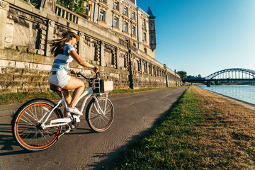 Fototapeta pretty woman ride bicycle on embankment of Wisla river obraz